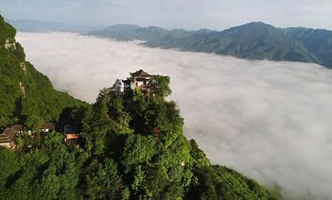 Jiutain taolais-temppeli näkyy selkeästi vuoren rinteellä, mutta alempana laaksossa paksut pilvet peittävät näkymän kiinalaisessa Hanzhongin maakunnassa tiistaina.