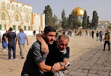 Palestiinalainen mies auttoi loukkaantunutta mielenosoittajaa 10. toukokuuta, kun yhteenotot kärjistyivät Israelin turvallisuusjoukkojen ja palestiinalaisten mielenosoittajien välillä al-Aqsan moskeijan edustalla.