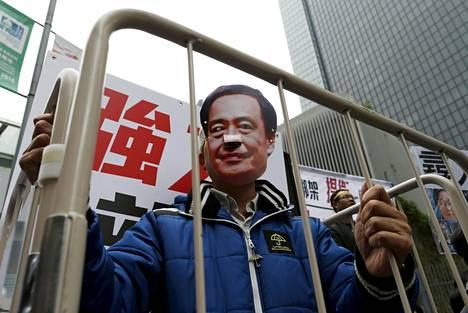 Mielenosoittaja oli sonnustautunut kadonnutta kirjakauppiasta Lee Pota esittämään naamariin Hongkongissa tammikuussa.