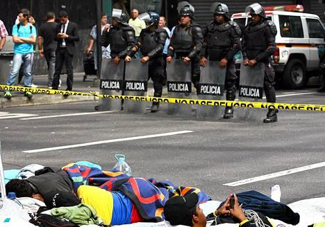 Opiskelijat osoittivat mieltään mellakkapoliisien edessä Caracasissa torstaina. Opiskelijoiden mielestä hallitus ei kerro totuutta presidentti Hugo Chávezin terveydentilasta.