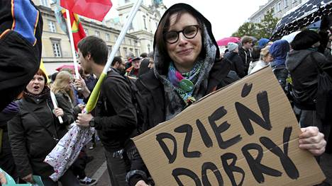 """Pakolaisten vastaanottamista kannattavat mielenosoittajat kokoontuivat Varsovassa syyskuussa 2015. Kyltissä lukee """"hyvää päivää""""."""