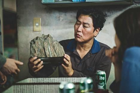Elokuva sysätään liikkeelle kun työttömien Kimien perhe saa lahjaksi vaurautta tuovan suseok-kiven. Onnenesinettä pitää käsissään perheen isä (Song Kang-ho).