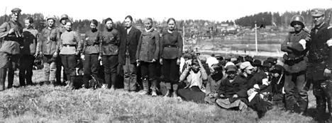 Vangittuja naiskaartilaisia matkalla Hennalaan 1918 saksalaisten ja suomalaisten sotilaiden vartioimina.