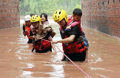 Pelastajat veivät lapsia turvaan tulvalta rankkasateiden piiskaamassa Kiinan Dazhoussa.