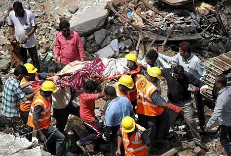 Pelastustyöntekijät etsivät eloonjääneitä romahtaneen kerrostalon jäänteistä Mumbaissa perjantaina.