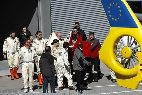 McLarenin työntekijät kätkivät Fernando Alonson lakanan taakse, kun häntä siirrettiin varikolta sairaalaan vievään helikopteriin.