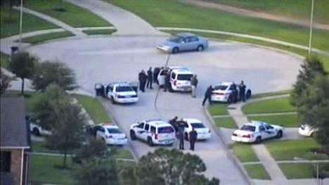 Videolta otetussa kuvankaappauksessa poliisijoukot ovat keskusteluyhteydessä autoonsa lukittautuneen epäillyn kanssa.
