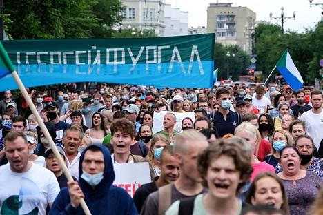 Mielenosoitukset saivat alkunsa, kun suosittu kuvernööri Sergei Furgal pidätettiin ja erotettiin viime kuussa. Kuvassa protestoijia kannattelemassa Furgalin nimeä kantavaa kylttiä 1. elokuuta Habarovskissa.