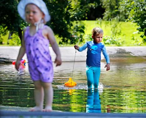 Kesäisesti pukeutunut Silvia Lehto (vas.) kahlasi ja Oskari Kristo uitti keltaista laivaa leikkipuisto Munkin vuotavassa altaassa Munkkiniemessä.
