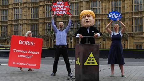 Boris Johnsoniksi pukeutunut mielenosoittaja uhkasi räjäyttää sopimuksettoman brexit-pommin Britannian parlamenttitalon ulkopuolella tiistaina. Toinen mielenosoittaja vaati kansanedustajia purkamaan pommin.
