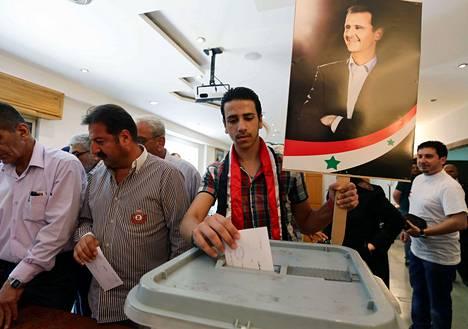 Presidentti Bashar al-Assadin kuvaa kantava mies äänesti Damaskoksessa tiistaina.