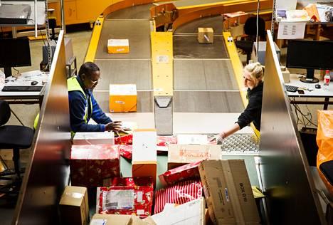 Elmi Hassan Ali ja Milja Koivurinta viime joulukuussa työssään Itellan logistiikkakeskuksessa Vantaalla.