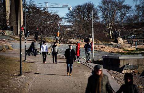 Ihmiset ulkoilivat aurinkoisessa säässä Eiranrannassa maaliskuun lopussa.