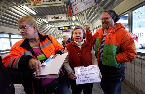 Lena Allen (vas.), Anja Sarre ja J-P Väisänen osoittivat mieltään kutojamummojen puolesta Malmin asemalla. Lassilassa asuva Sarre käy itsekin tekemässä käsitöitä Malmilla.