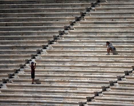 Turistit ottivat valokuvia Ateenan Panathenean-stadionilla kesäkuussa.