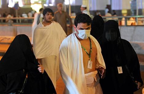 Pyhiinvaeltajista osa piti varmuuden vuoksi hengityssuojaa, kun he saapuivat aamurukoukseen Mekan suureen moskeijaan.