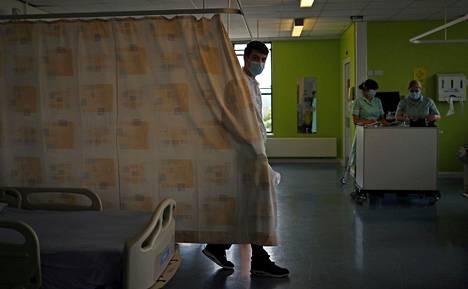 Sydänhoito-osaston hoitaja Cavan Smith laittoi verhoja näkösuojiksi potilasvuoteiden väliin.