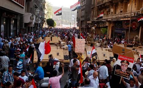 Sotilaat vartioivat Kairossa Tahririn aukiolle vievää tietä perjantaina. Aukiolle kerääntyi iltaan mennessä kymmeniätuhansia armeijaa tukevia ihmisiä.