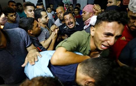 Israelilaissotilaiden tulituksessa kuolleen palestiinalaisen läheiset kokoontuivat gazalaisen sairaalan ruumishuoneelle perjantaina.