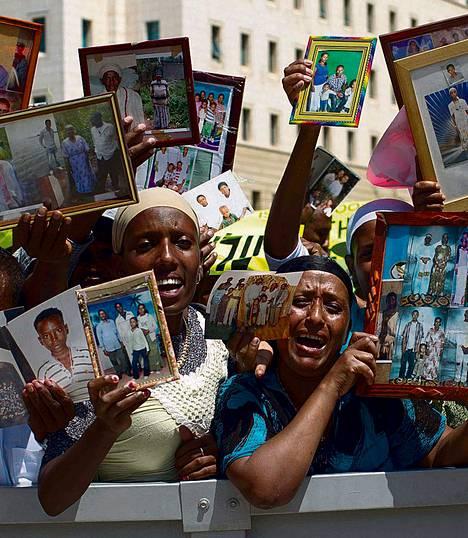 Israelin etiopialaiset pitelivät Etiopiaan jääneiden omaistensa kuvia pääministerin toimiston edessä keskiviikkona.