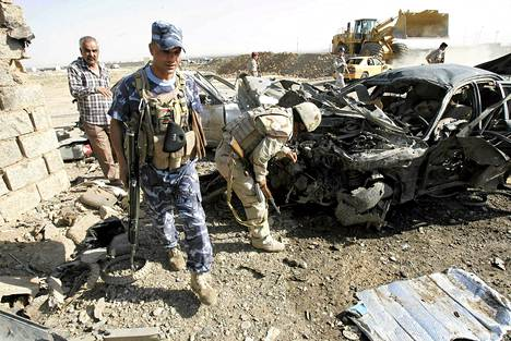 Turvallisuusmiehet tutkivat autopommin tuhohja Kirkukissa sunnuntaina.