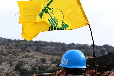 Sinikypäräinen YK:n rauhanturvaaja tarkkaili sunnuntaina Libanonin ja Israelin välistä rajaa Libanonin puolelta Meiss al-Jabalin kylästä vieressään shiiajärjestö Hizbollahin lippu.