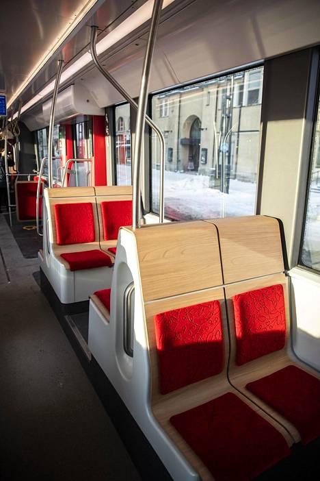 Penkit on päällystetty vaalealla puusävyllä ja punaisella kankaalla. Sisällä on avaraa. Tampereen ratikkavaunu on pidempi ja leveämpi kuin Helsingin ratikka.
