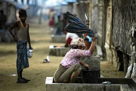 Rohingya-kansaan kuuluva nainen pesi vaatteitaan pakolaisleirissä Sittwen ulkopuolella Myanmarissa 21. toukokuuta.