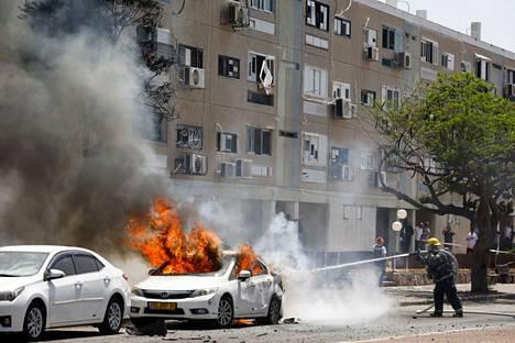 Israelilaiset palomiehet sammuttivat autoa, joka oli syttynyt tuleen Gazasta ammutusta raketista tiistaina Askalonissa.