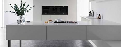Tilaa ja avaruutta keittiöön luodaan kalusteisiin integroiduilla kodinkoneilla ja aamiaiskaapilla, johon pienkoneet saa pois tasoilta piiloon.