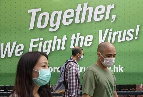Hengityssuojaimin varustautuneet hongkongilaiset kulkivat koronavirusaiheisen julisteen ohi sunnuntaina.