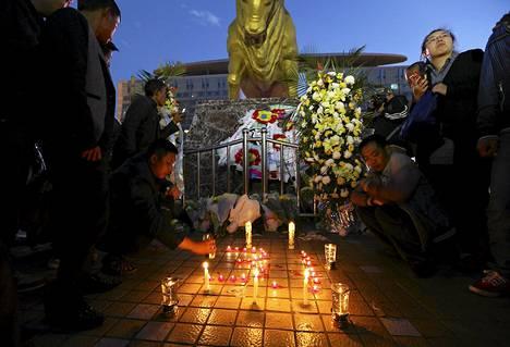Ihmiset sytyttivät kynttilöitä Kunmingin veitsi-iskun jälkeen rautatieaseman ulkopuolella sunnuntaina.
