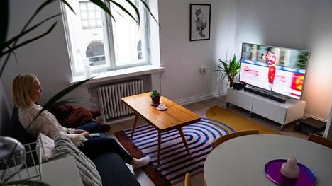 Noora Vuorimies katsoo televisiota kotonaan Helsingissä. Kuvassa näkyvät keittiöryhmä, sohvapöytä ja tv-taso ovat kaikki löytyneet uuteen kotiin internetin myyntipalveluista.