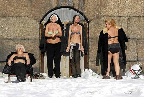 Naiset nauttivat auringosta Pietari-Paavalin linnoituksen seinustalla Pietarissa.