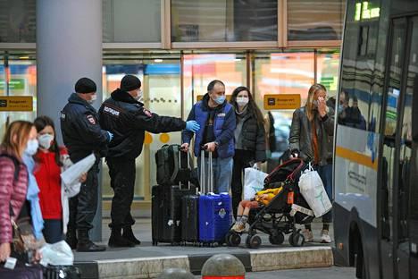 Poliisit ohjasivat saapuneita matkustajia sunnuntaina Šeremetjovin lentokentällä Moskovan ulkopuolella.
