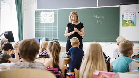 """""""Kynät voi jättää kynäkouruun ja penaalin laittaa nyt pois"""", Töölön ala-asteen koulun opettaja Minna Sulander ohjeistaa. Ensimmäisinä koulupäivinä ekaluokkalaisilla on vielä totuttelemista pelkkään luokkahuoneeseen, mutta pian Sulander ottaa käyttöön myös käytävätilaa ja sen kalusteita."""