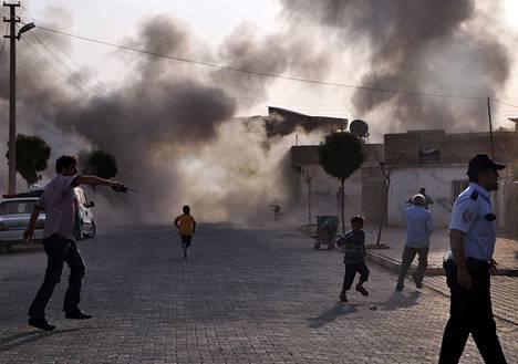 Savu kohosi tuhoutuneiden rakennusten ylle Syyrian puolelta kantautuneen tulituksen jälkeen Akçakalen kylässä keskiviikkona.
