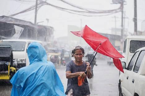 Manilalaisnainen yritti suojautua sateenvarjolla Filippiineille lauantaina iskeneneitä rankkasateita vastaan.