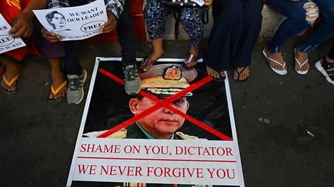 Myanmarilaiset mielenosoittajat vastustivat vallan kaapannutta sotilasjunttaa mielenosoituksessa 11. helmikuuta Yangonissa. Kuvassa rastitettuna juntan johtaja, kenraali Min Aung Hlaing.