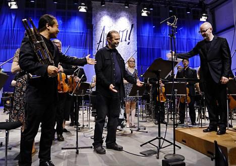 Wu Wei, säveltäjä Jukka Tiensuu ja kapellimestari Baldur Brönnimann kamariorkesteri Avantin kanssa aplodien aikaan.