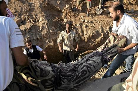 Ihmiset hautasivat kaasuiskuksi väitetyssä hyökkäyksessä kuolleen ruumista Damaskoksessa.