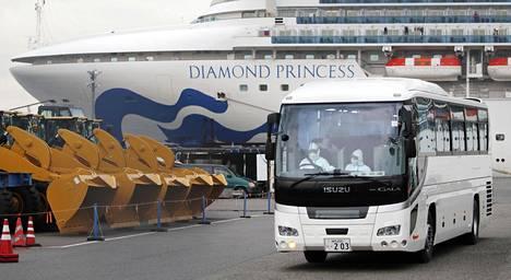 Suoja-asuun pukeutunut kuljettaja ajoi linja-autoa perjantaina 14. huhtikuuta lähellä Japanissa karanteenissa olevaa Diamond Princess -alusta.