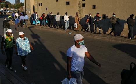 Ihmiset kävelevät töistä kotiin Sowetossa, Etelä-Afrikassa maanantaina.