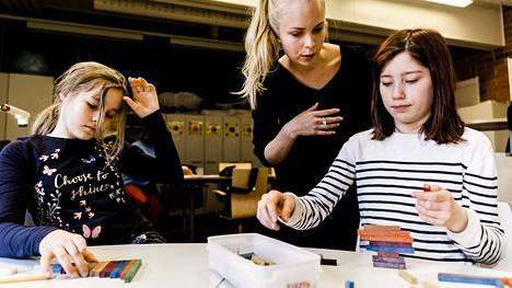 Neljäsluokkalaiset Elisa Tuppurainen (vas.) ja Miisa Leinonen opettelivat murtolukuja värisauvojen avulla. Harjoittelija Emma Juntunen opasti.