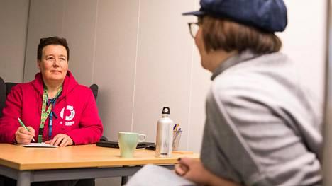 """Opinto-ohjaana työskentelevä Tiina Parviainen neuvoi asiakasta Ohjaamossa keskiviikkona. Hän aloittaa tapaamisen nuoren kanssa kysymällä: """"Mitä sulle kuuluu?"""""""