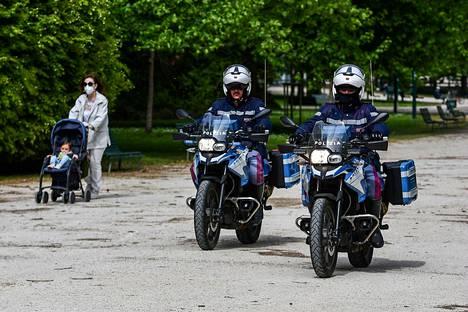Poliisit valvoivat ihmisten käyttäytymistä milanolaisessa Sempionen puistossa.