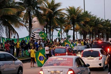 Äärioikeiston ehdokkaan Jair Bolsonaron kannattajia oli kokoontuneena Rio De Janeirossa sunnuntaina. Kuvassa näkyy myös ilmalla täytetty vankila-asuinen, joka halventaa maan entistä, vankilaan tuomittua presidenttiä Luiz Inácio Lula da Silvaa eli Lulaa.