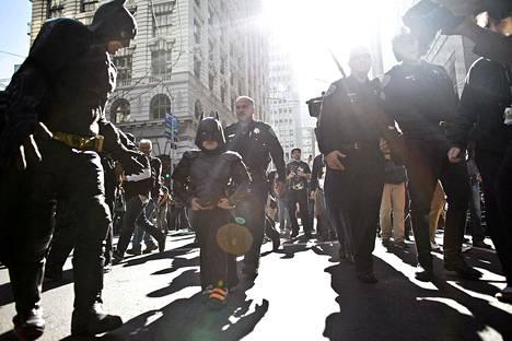 Poliisi saattelee Batkidiä ja Batmania heidän pidätettyään Arvuuttajan.