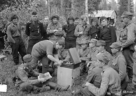 Saksalaisia panssarivaunu- ja suomalaisia jalkaväkisotilaita kuuntelemassa veljellisesti gramofonia Raatteen tiellä Suomussalmella 27. kesäkuuta 1941.