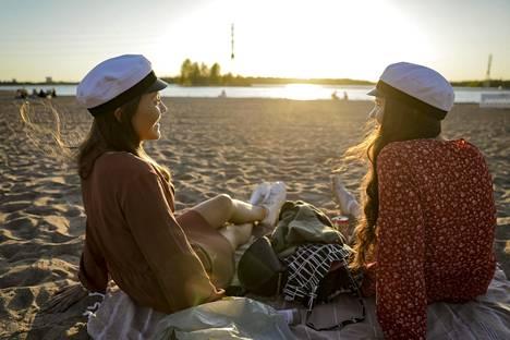 Iltaa kohti puistoissa ja rannoilla alkoi näkyä enemmän valkolakkeja. Anni Pilviniemi (vas.) ja Mai Smolander kirjoittivat ylioppilaaksi Lauttasaaren yhteiskoulun lukiosta.